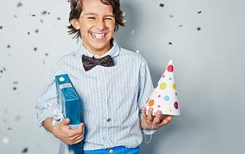 A boy holding a birthday present and birthday hat laughing while confetti is falling in the air