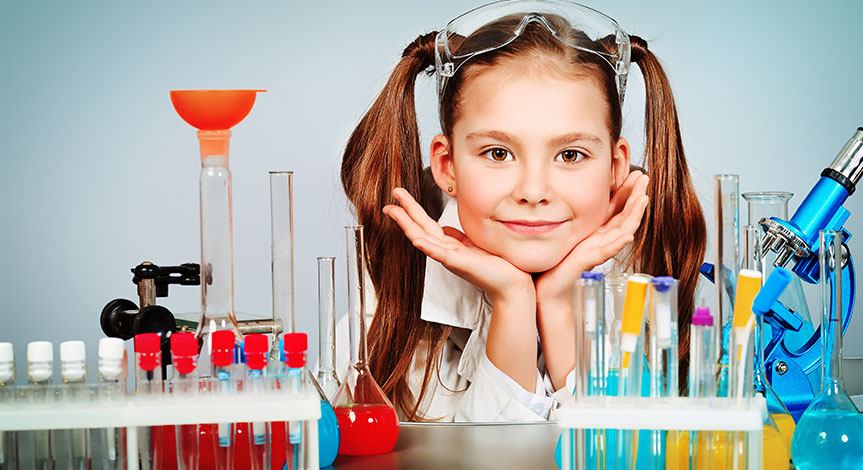 Science Girl with hands under her chin with multi colored test tubes in front of her.